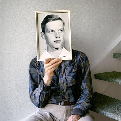 """Birthe Piontek: Abendlied, """"Two Dads"""" - Mein Vater auf der Treppe in unserer Haus. Er posiert mit einem frühen Foto von sich."""
