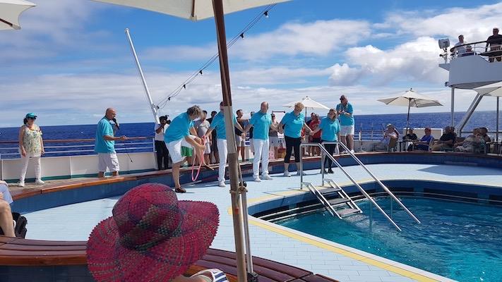Das Leben an Bord war ausgesprochen lustig: Das Team des Reiseveranstalters versucht, den Hula-Hoop-Reifen durchzugeben, ohne dabei die Hände loszulassen. Am Mikrofon: Sportskanone Franky